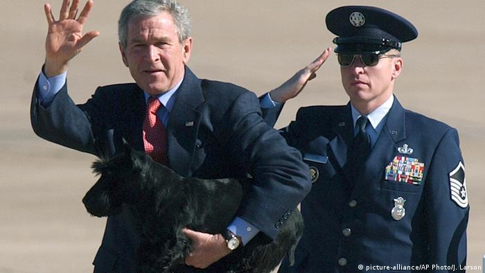 Former US President George W. Bush with his dog Barney (picture-alliance/AP Photo/J. Larson) and a saluting soldier