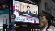 HONG KONG, CHINA - SEPTEMBER 04: People walk past a big screen replaying Hong Kong Chief Executive Carrie Lam announcing the formal withdrawal of the extradition bill on September 04, 2019 in Hong Kong, China. Hong Kong's embattled leader Carrie Lam announced the formal withdrawal of the controversial extradition bill on Wednesday, meeting one of protesters' five demands after 13 weeks of demonstrations which became the biggest political crisis since Britain handed its onetime colony back to China in 1997. (Photo by Chris McGrath/Getty Images)