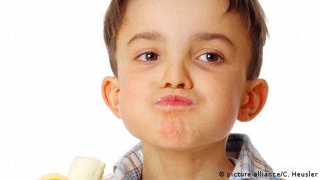 Ein Junge isst eine Banane und hat die Backen dick.(picture-alliance/C. Heusler)