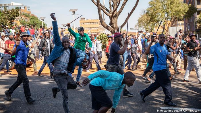 Residents of Jeppe township wave batons after a new wave of violence against foreigners