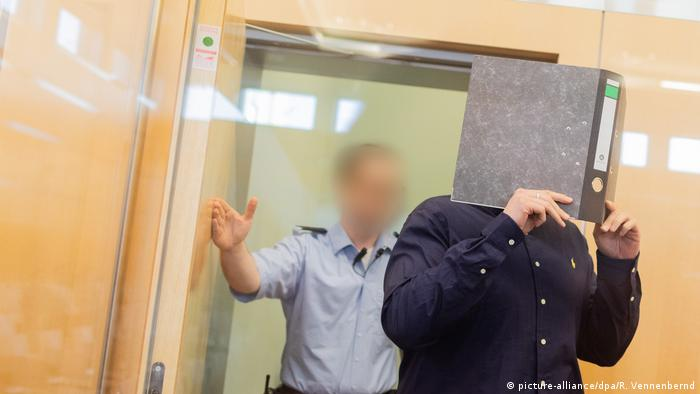 Nils D covers his face with a binder as he arrives for trial on terrorism-related offenses (picture-alliance/dpa/R. Vennenbernd)