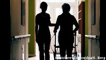 A carer and a resident of an aged care home seen in silhouette from back (picture-alliance/dpa/O. Berg)