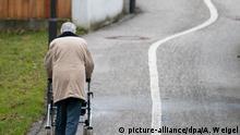 ARCHIV - 16.01.2014, Bayern, Landshut: Eine ältere Frau geht mit einem Rollator auf einem Weg entlang. Foto: Armin Weigel/dpa +++ dpa-Bildfunk +++ | Verwendung weltweit