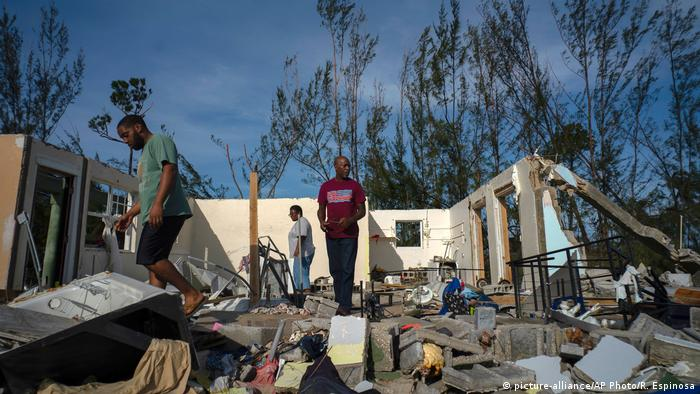 George Bolter, left, and his parents walk through the remains of his home destroyed by Hurricane Dorian in Freeport, Bahamas