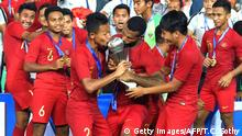 ARCHIV 26.02.2019 *** Indonesian midfielder Sani Riski Fauzi (L) and forward Marinus Wanewar (R) kiss the championship trophy as the team celebrate after winning the AFF U-22 Cup 2019 finals football match between Indonesia and Thailand at the National Stadium in Phnom Penh on February 26, 2019. (Photo by TANG CHHIN Sothy / AFP) (Photo credit should read TANG CHHIN SOTHY/AFP/Getty Images)