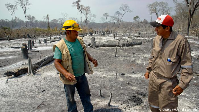 Firefighters Moises Soria Valverde and Ronald Picolomini stand in a burnt-out area in Santa Rosa de Tucabaca (DW/Juan Gabriel Estellano)