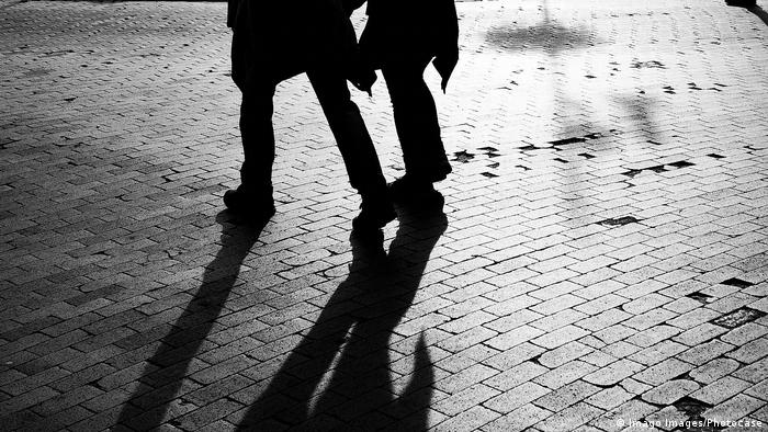 Black-and-white image of man and woman moving over a pavement