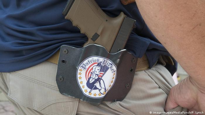 Пистолет на поясе и наклейка с флагом США