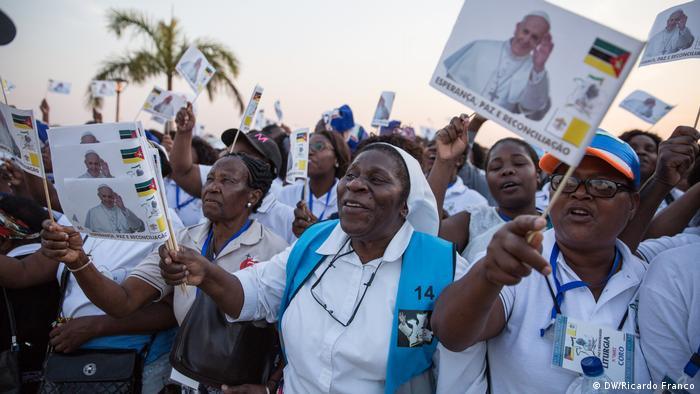 Papst-Anhänger schwenken Fahnen mit dem Bild des Papstes