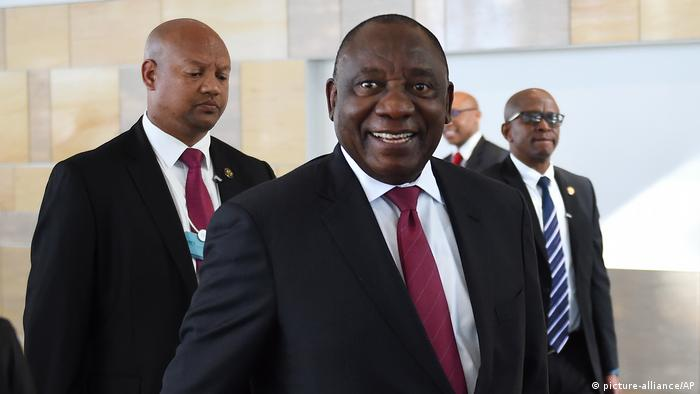 South Africa's President Cyril Ramphosa walks in suit and smiles to the camera