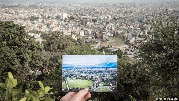 A hand holding an old photograph of Kathmandu in front of the same view of the city today