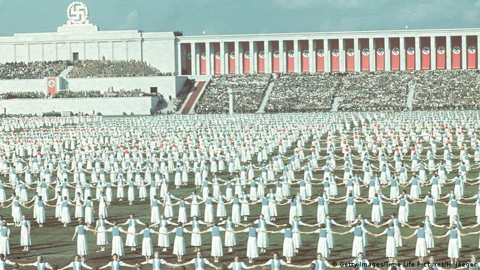 Hundreds of girls holding hands in a large field, Nazi architecture and swastika in the background (Getty-Images/Time Life Pictures/H. Jaeger)