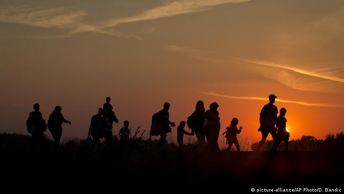 Refugees from the Middle East are silhouetted against the setting sun as they walk on railway tracks from Serbia