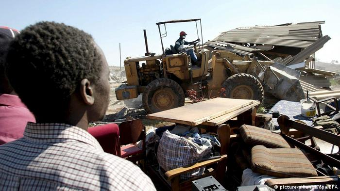 A resident of Kambuzuma township watches an earthmover destroy a house on Friday, 03 June 2005.