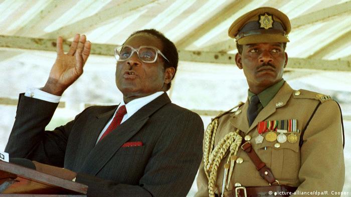 Der ehemalige Präsident Simbabwes, Robert Mugabe, steht neben einem General und hält eine Rede vor schwarzen Dorfbewohnern bei der Übergabe einer kommerziellen Farm in weißem Besitz zur Umsiedlung im Jahr 1998