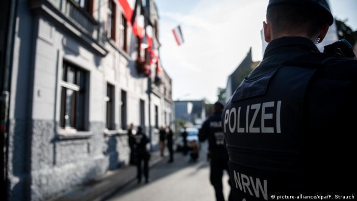 Police watch graffiti artists spray a wall