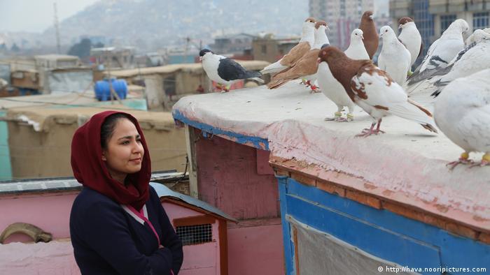 Eine junge Frau blickt auf eine Gruppe Tauben auf einem Dach. Szene aus dem Film Hava, Maryam, Ayesha von Sahraa Karimi