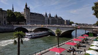 People sitting at a street café along the River Seine in Paris, France