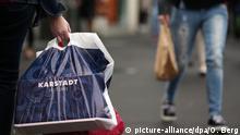 ARCHIV - 15.08.2014, Nordrhein-Westfalen, Düsseldorf: Eine Frau geht mit einer Karstadt-Tüte durch die Stadt. Immer mehr Händler in Deutschland verbannen die Plastiktüte aus ihren Geschäften. Jetzt hat der Warenhausriese Karstadt Kaufhof den Komplettausstieg beschlossen. Innerhalb des ersten Halbjahres 2020 sollen die letzten Bestände an Einwegplastiktüten kontinuierlich reduziert werden, kündigte das Unternehmen am Montag an. Foto: Oliver Berg/dpa +++ dpa-Bildfunk +++   Verwendung weltweit