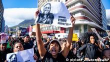 04.09.2019, Südafrika, Cape Town: Eine Frau hält während eines Protestes ein Schild mit dem Bild der kürzlich vergewaltigten und getöteten 19-jährigen Studentin der Universität Kapstadt, Uyinene Mrwetyana, in die Luft. Unmittelbar vor dem Start der Afrikatagung des Weltwirtschaftsforums (WEF) in Kapstadt haben hunderte Südafrikanerinnen gegen die grassierende Gewalt gegen Frauen im Land demonstriert. Foto: -/AP/dpa +++ dpa-Bildfunk +++