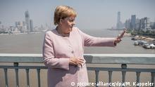 07.09.2019, China, Wuhan: Bundeskanzlerin Angela Merkel (CDU) steht auf der Brücke über den Chang Jiang Fluss (ehemals Jangtsekiang, Langer Fluss). Merkel ließ die Kolonne bei der Fahrt vom Flughafen in die Stadt am Fluss stoppen, um sich von der Brücke aus den Fluss und das Stadtpanorama anzuschauen. Foto: Michael Kappeler/dpa +++ dpa-Bildfunk +++
