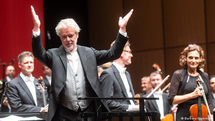 Jukka-Pekka Saraste accepting ovations with orchestra musicians standing (Barbara Frommann)