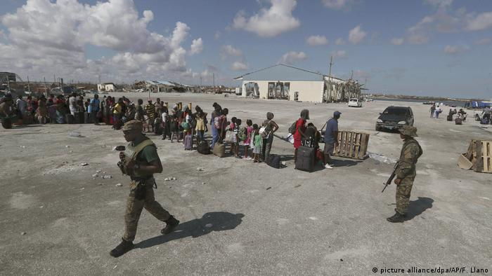 Survivors in Abaco's Marsh Harbor line up to evacuate on Saturday