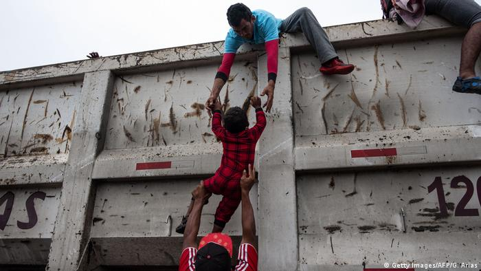 Migrants help a boy hitch a ride on a truck in Mexico (Getty Images/AFP/G. Arias)