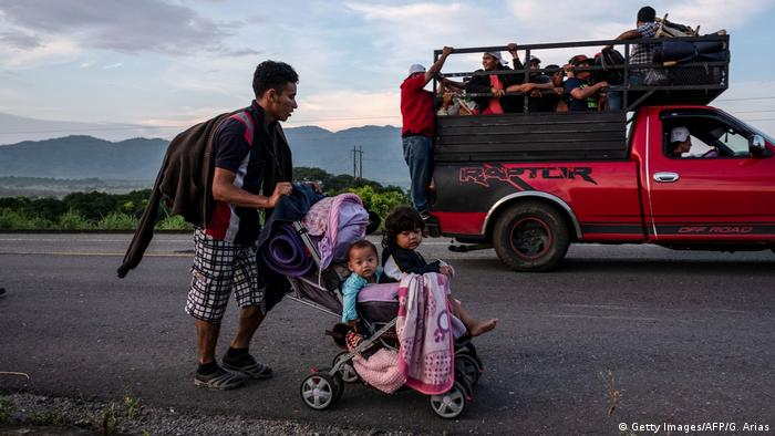 Guillermo Arias' photo showing a truck of people in the background and a man pushing two children in a stroller (Getty Images/AFP/G. Arias)