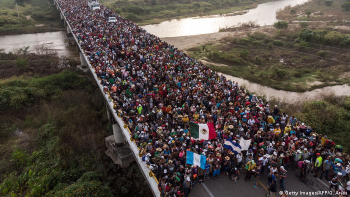 Eine unüberschaubare Menschenmenge mit verschiedenen mittelamerikanischen Flaggen auf einer Brücke über einem Fluss