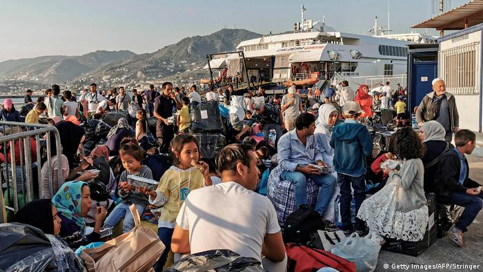 Migrants and refugees wait to board a ship at the port of Mytilene (Getty Images/AFP/Stringer)