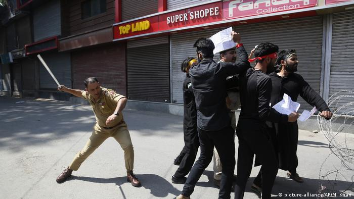An Indian police officer beats Kashmiri Shiite Muslims as they attempt to take out a religious procession during restrictions in Srinagar