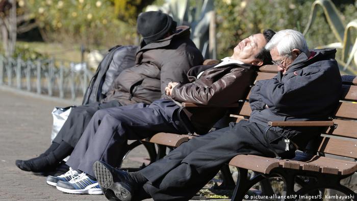 Mittagsschlaf auf einer Parkbank in Tokio