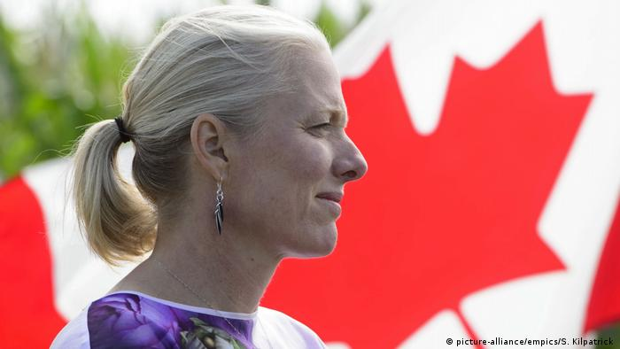 Catherine McKenna with the Canadian flag