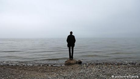 A man stands in front of a body of water