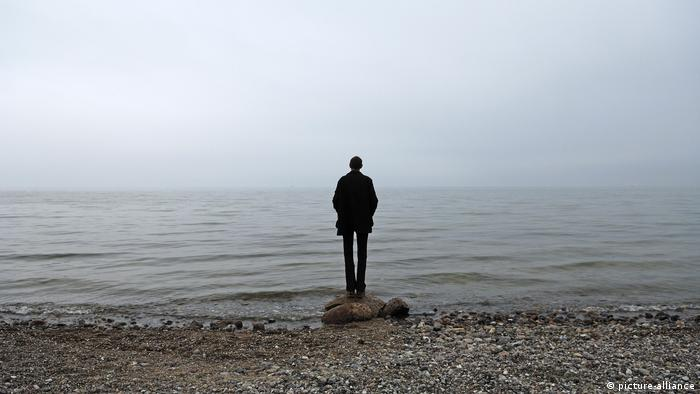A man standing alone at the water's edge