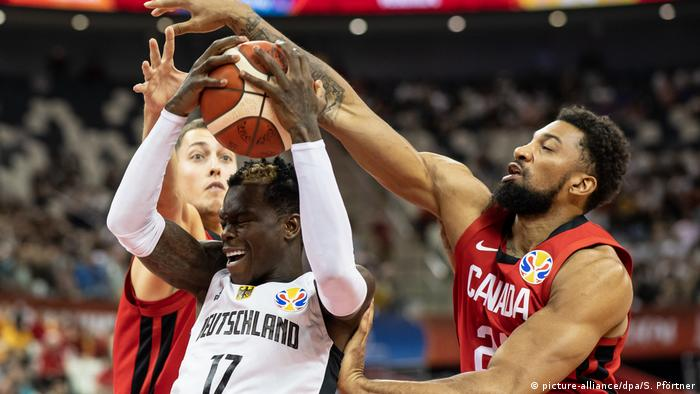 Basketball World Cup 2019, Dennis Schröder is blocked by two Canadian players, Kyle Wiltjer and Khem Birch; September 9. (picture-alliance/dpa/S. Pförtner)