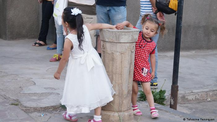 Children playing at water fountain, Armenia