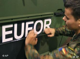 Ein Soldat der Bundeswehr beklebt ein Fahrzeug mit dem Schriftzug EUFOR (Archivfoto: ap)