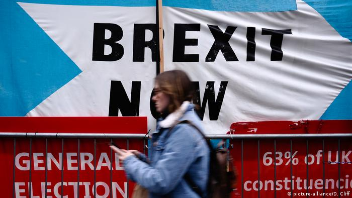 A woman walks past a Brexit Party banner calling for 'Brexit Now' outside the Houses of Parliament in London