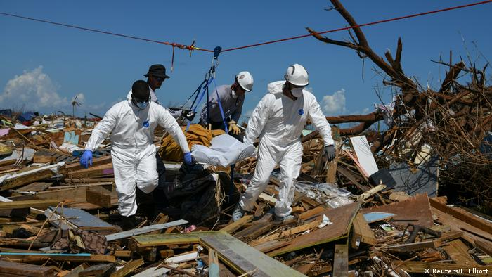 Personnel from the Royal Bahamas Police Force and a U.S. urban search and rescue team remove a body recovered in a destroyed neighbourhood