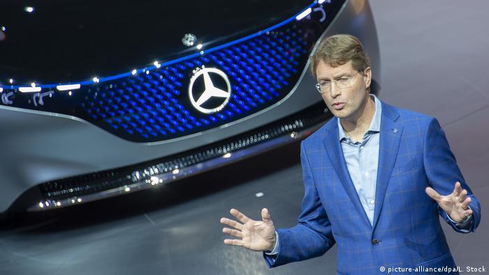 Daimler chairman Ola Källenius holding a speech in front of a Mercedes electric car