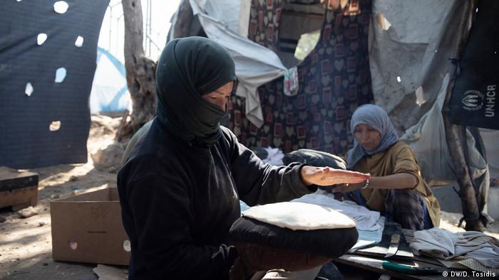 A woman in a refugee camp making bread