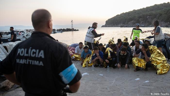 A policeman at the docks in Lesbos supervising a group of refugees