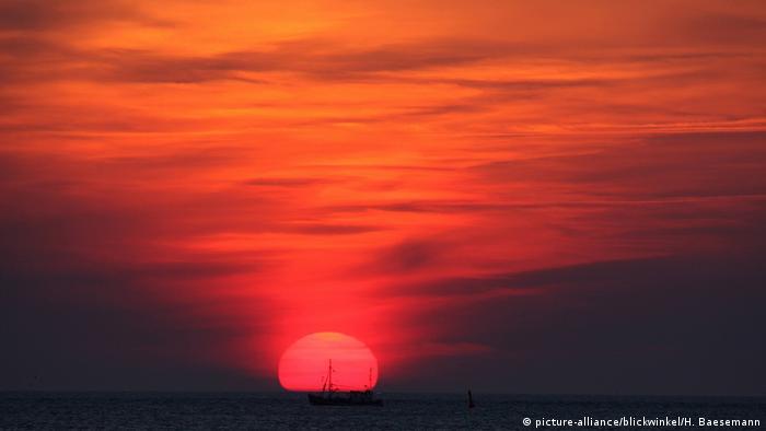Рыболовецкий катер перед островом Лангеог во время заката