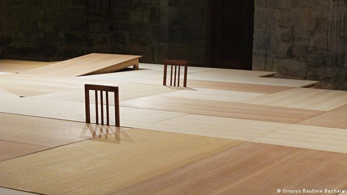 Eine lange breite Holzfläche, woraus zwei leere Stuhllehen herausragen