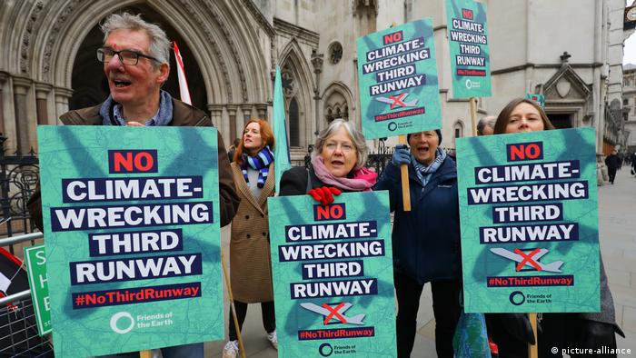 Protesters hold placards that read: No climate-wrecking third runway