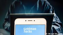A Goldman Sachs logo can be seen on a phone screen.