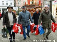 Three men carrying plastic shopping bags