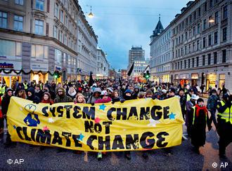 Activists marching in downtown Copenhagen with a banner that reads, System change not climate change